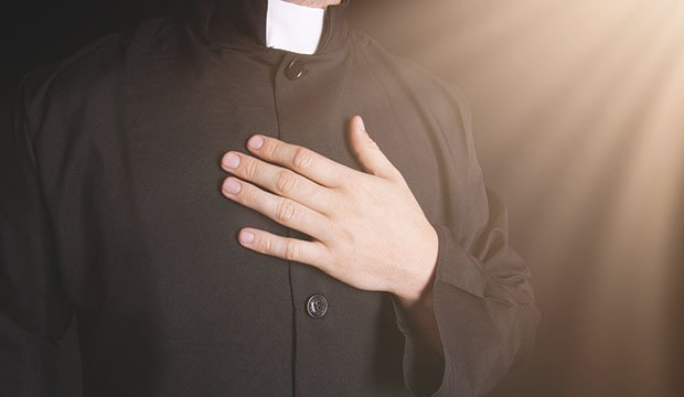 Priest hand on his chest