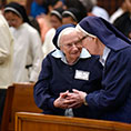 Sr. Rita Claire Davis, left, shakes the hand of Sr. Mary Michael Dittoe, right, as she gives the sign of peace during the 200th Anniversary as a congregation of the Sisters of St. Mary of Namur,