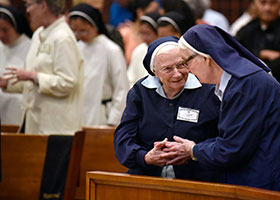 Sr. Rita Claire Davis, left, shakes the hand of Sr. Mary Michael Dittoe, right, as she gives the sign of peace during the Mass.