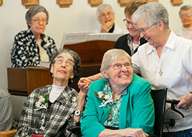 Sister Joan Markey and Sister Mary Elaine Breen, celebrating 65 years of their vows, are greeted by well wishers during the sign of peace as  Bishop Michael Olson celebrates Mass five sisters to the Sisters of Saint Mary of Namur, Sunday, September 15, 2019.