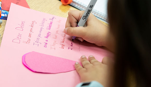 A Holy Trinity Catholic School student writes a Valentine's Day card for the elderly in a nursing home January 27.