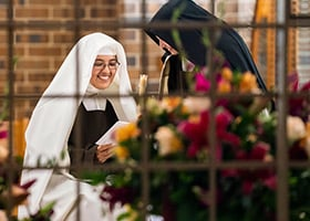 Sister Teresa Agnes hands a candle to Sister Maria Sagrario prior to the Mass of Thanksgiving Nov. 9 at Arlington Carmel. (NTC/Juan Guajardo)