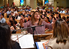Choir director Ruth Yammine conducts the St. Francis of Assisi choir during Sunday Mass April 7 in Grapevine. (NTC/Ben Torres)