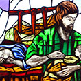 stained glass showing St. Joseph holding baby Jesus while Mary sleeps