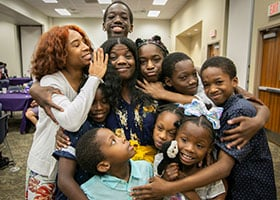 Meesha Robinson poses with nine of her 12 children during a graduation party for participants in the Stay the Course program at Catholic Charities, Thursday, June 6, 2019. (NTC/Rodger Mallison)
