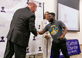 Catholic Charities CEO and President Michael P. Grace congratulates Bonane Amosi, who earned an Associate of Arts degree in Philosophy from TCC Trinity River. (NTC/Rodger Mallison)