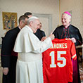 Pope Francis gives a thumbs up as he looks at a football jersey presented by Bishop James V. Johnston Jr. of Kansas City-Saint Joseph, Mo