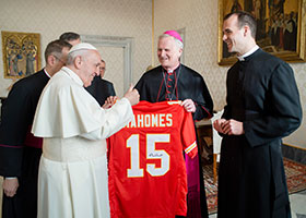 Pope Francis gives a thumbs up as he looks at a football jersey presented by Bishop James V. Johnston Jr. of Kansas City-Saint Joseph, Mo., during a meeting with U.S. bishops from Iowa, Kansas, Missouri and Nebraska.