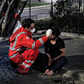 homeless man treated by red cross worker