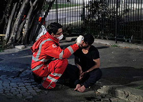 red cross worker helping a homeless man