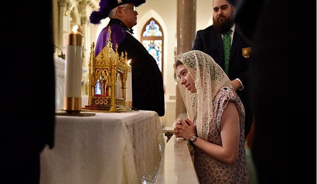 Margery Pyle, of St. John Paul II Parish in Denton, kneels before the relic of St. Jean Vianney at St. Patrick Cathedral in Fort Worth, May 16, 2019. (NTC/Ben Torres)