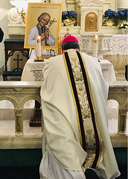 Bishop Michael Olson kneels before the heart of St. Jean Vianney (NTC/Joan Gillen)