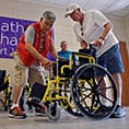 Knights Roy Shelton, left, and Jack McGeough unfold a wheelchair after donating several to Catholic Charities Fort Worth, June 22, 2018. (NTC photo/Ben Torres)