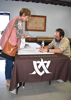 Dan Burke, presenter at the Into the Deep retreat in Windthorst, signs his book for Joyce Wolf