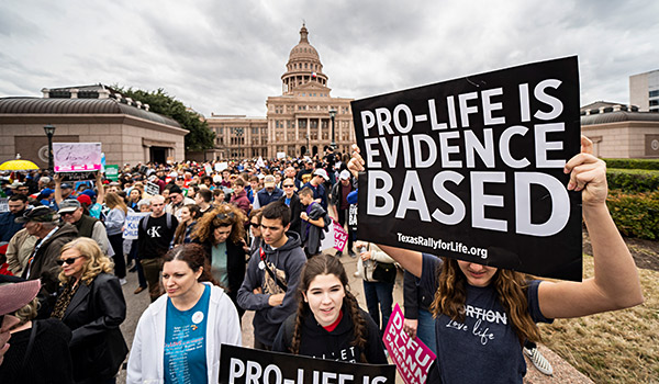 Dozens of youth from St. Elizabeth Ann Seton Parish in Keller hold up signs as they wait outside the Texas Capitol prior to the 2020 Texas March and Rally for Life. (NTC/Juan Guajardo)