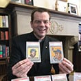Fr. Ubel holds two baseball cards