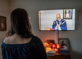 a woman watches Mass on livestream