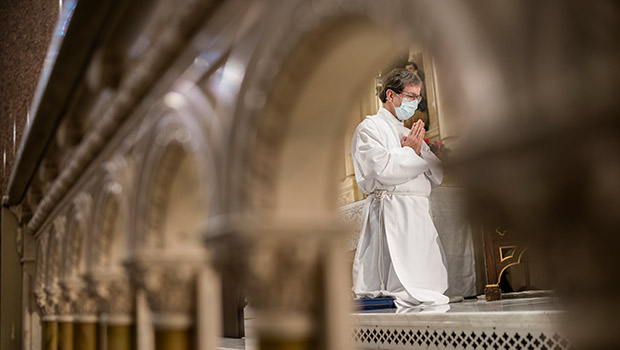 A minister kneels during daily Mass at St. Patrick Cathedral April 28. Beginning May 2-3, public celebration of Mass will return in the Diocese of Fort Worth. (NTC/Juan Guajardo)