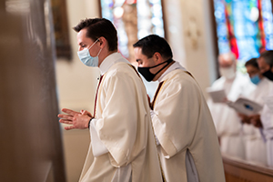 Deacons Jason Allan and Joseph Moreno are showing wearing masks during vespers at St. Patrick Cathedral. (NTC/Juan Guajardo)