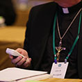 bishop holding electronic device