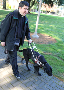 Tony Del Castillo, a second-year theology student for the Diocese of Orange, Calif., walks with his guide dog, Dagwood, toward the church at Mount Angel Seminary in St. Benedict, Ore., Oct. 1, 2019.