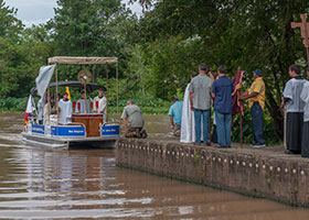 A priest, members of the Knights of Columbus and lay Catholics greet an arriving boat with altar servers during the Aug. 15, 2017, Fete-Dieu du Teche procession in Arnoldville, La.