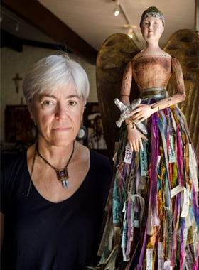 "Artist Deborah McCullough poses June 19 with her work ""Angel of Mercy,"" whose skirt is made up of ribbons, each bearing the name of a person who has died in the Sonoran Desert from 2011 through February 2012. The work was on display at the St. Thomas Mor e Catholic Newman Center on the campus of the University of Arizona in Tucson. (CNS photo/Gary O'Brien)"