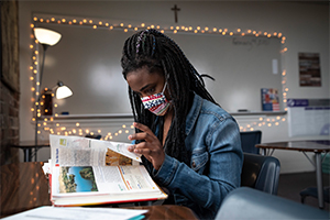 Fiona Schoonover reads from a book while taking notes in a social studies class at Cassata Catholic High School in Fort Worth, on Thursday, Feb. 04, 2021.