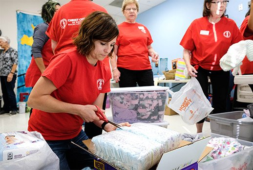 Lindsay Laubacher helps organize baby supplies during a meeting of the Christ Child Society at St. Philip the Apostle Church in Lewisville Oct. 18. (NTC/Kevin Bartram)