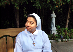 Postulant Iliana Maldonado sits near a statue of St. Francis outside the Monastery of St. Veronica Giuliani in Wilmington, Del., Sept. 23. The 21-year-old from Guatemala is living in the community of cloistered Poor Clare nuns to see if she is called to become a nun and follow the order's life of poverty and service as begun in the 12th century by St. Francis and his followers, including St. Clare. (CNS photo/Tyler Orsburn)