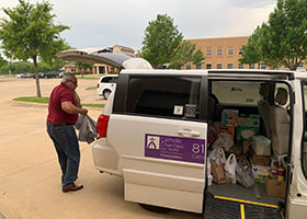 Ric DeLeon (in red shirt) loading items into a CCFW transportation van to be sent to the pantries.