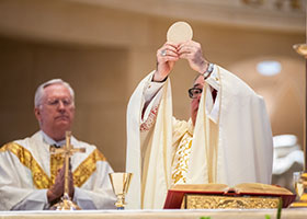 Bishop Olson raises the host during the Liturgy of the Eucharist at the Corpus Christi Mass celebrated at St. Elizabeth Ann Seton Parish. (NTC/Juan Guajardo)