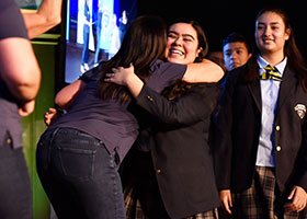"Brissa Gutierrez receives as hug as she's ""drafted"" to an employer during the 2019 Cristo Rey Draft Day at school's new campus on Altamesa Boulevard in south Fort Worth Aug. 16. (NTC/Ben Torres)"
