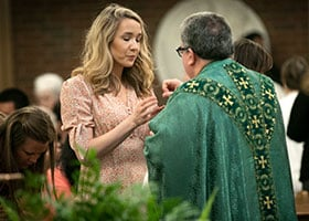 A young woman receives Communion from Bishop Michael Olson during a Mass dedicated to single people at St. Michael Parish in Bedford July 27, 2019. (NTC/Rodger Mallison)