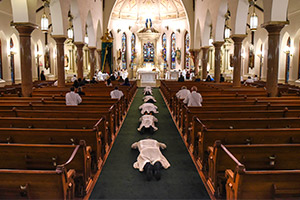men prostrate at altar