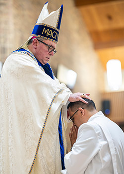 Bishop Olson places his hands on the head of Pedro Martinez and invokes the power of the Holy Spirit.