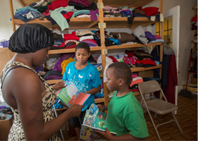 Katrina Robinson and her two sons, David Collins, 11, and Dabion Collins, 7, look through books at St. Dominic Outreach Center in Detroit Aug. 7. Since May, on the nights when they are unable to crash with family or friends, the family car is the only sh elter Robinson and her two young sons have. (CNS photo/Jim West)