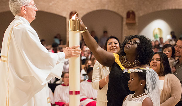 woman lights Easter candle at St. Joseph Parish