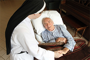 A patient is pictured in a file photo chatting with a nun at Rosary Hill Home, a Dominican-run facility in Hawthorne, N.Y., that provides palliative care to people with incurable cancer and have financial need. (CNS photo/Gregory A. Shemitz)