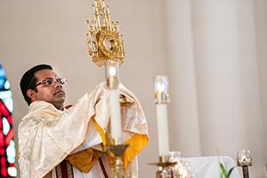 Father John Perikomalayil Antony, HGN, gives a benediction during a recent livestreamed Adoration hour at St. Joseph Parish in Rhineland. (NTC/Juan Guajardo)