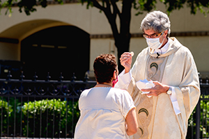 Father Tim Thompson gives Communion to a parishioner outside of Immaculate Conception Catholic Church in Denton May 17. (NTC/Kenneth Munyer)