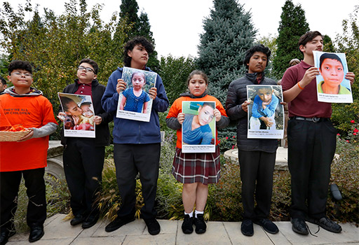Students from Our Lady of Guadalupe School in Chicago are seen Oct. 16, 2019, holding pictures of detained immigrant children who have died. The children were remembered during a prayer service at Holy Family Church. (CNS photo/Karen Callaway, Chicago Catholic)
