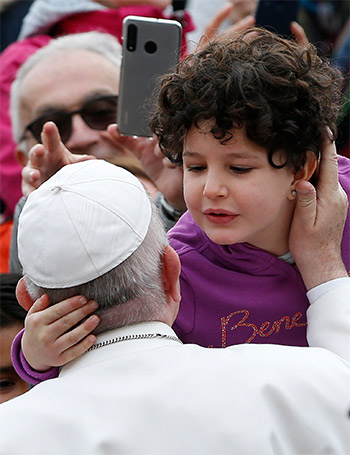 Pope Francis greets a child during his general audience in St. Peter's Square at the Vatican Feb. 26, 2020. (CNS photo/Paul Haring)