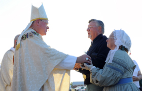 New York Cardinal Timothy M. Dolan receives the offertory gifts from Civil War re-enactors during Mass on the grounds of Xavier Center in Gettysburg, Pa., July 6. The outdoor service marked the 150th anniversary of the Battle of Gettysburg, during which the local St. Francis Xavier Church served as a hospital for wounded soldiers. (CNS photo/Emily M. Albert, The Catholic Witness)