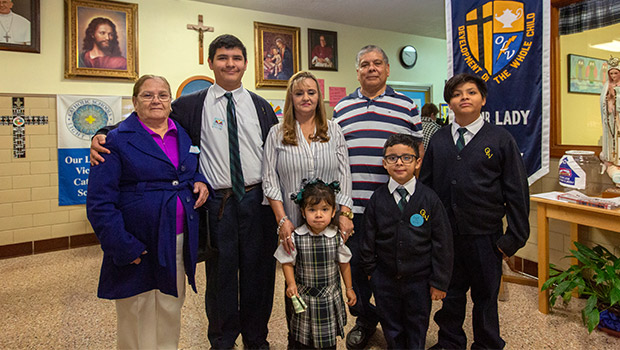 Left to right: Grandmother Eduarda Lopez, Cesar Lopez, 14, grandmother Nelda Ramirez, with Marissa Lopez, age 3, grandfather Gabriel Ramirez, Christian Lopez, age 7, and Gavin Lopez, age 10, during Grandparents Day at Our Lady of Victory Catholic School Jan. 29, 2020. (NTC/Rodger Mallison)