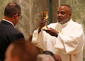Deacon offers chalice to communicant