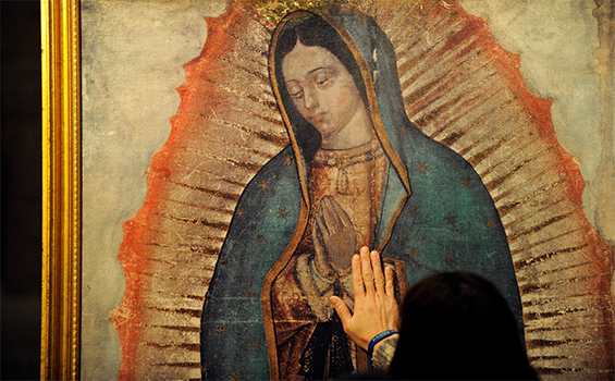 A woman lays her hand on a traveling missionary image of Our Lady of Guadalupe during a visit by the replica to St. Louis Church in Pittsford, N.Y. The digital image is a reproduction of the image left on the tilma of St. Juan Diego in present-day Mexico City in 1531. (CNS photo/Mike Crupi, Catholic Courier)