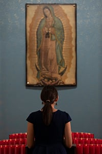 A young woman prays before an image of Our Lady of Guadalupe in Holy Cross Parish in The Colony. (NTC/Juan Guajardo)