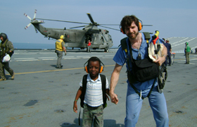 Heyne assists a child on the Cavour, an Italian aircraft carrier off the coast of Port-au-Prince, Haiti, following the devastating earthquake in 2010. The ship provided an operating room and a computed tomography (CT) scanner for earthquake victims. Heyne helped transport patients and served as an interpreter between Italian and U.S. physicians. •
