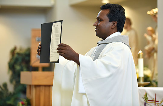 Father Wilson Lucka smiles as he holds an official document declaring him the new parish's pastor during a dedication Mass at Holy Trinity Parish in Azle June 16. (NTC/Ben Torres)
